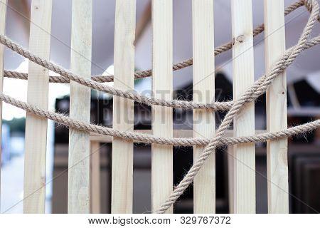 Abstract background close up Arranging rope on wood texture boards. brown nautical knotted rope on wooden planks. Jute rope. sisal brown natural background. Partition wooden wall decor. Rustic. Loft stock photo