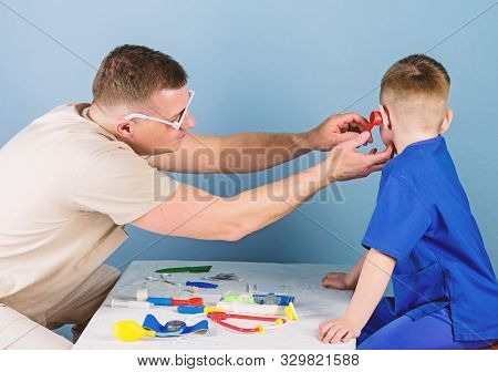 Hospital worker. Medical service. Man doctor sit table medical tools examining little boy patient. Health care. Pediatrician concept. Careful pediatrician check health of kid. Medical examination stock photo