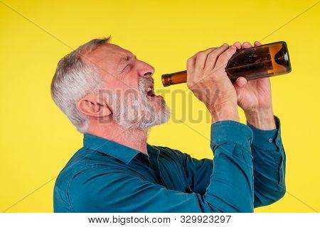 senior man drinking alcohol alone studio yellow baclground stock photo