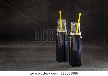 Bottles with detox activated charcoal black lemonade on table. Healthy lifestyle drink. Natural hangover cure stock photo