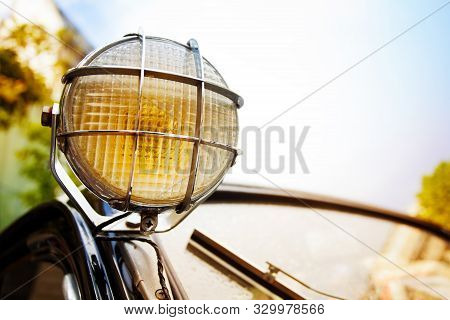 Close up of old head light on rarity black car stock photo