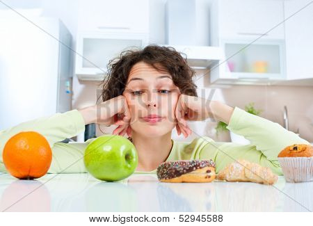 Diet. Dieting concept. Healthy Food. Beautiful Young Woman choosing between Fruits and Sweets. Weigh