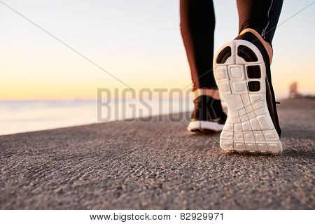 Runner man feet running on road closeup on shoe. Male fitness athlete jogger workout in wellness