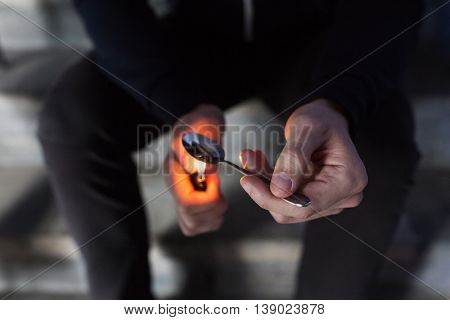 drug use, crime, addiction, substance abuse and people concept - close up of addict with lighter and spoon preparing dose of crack cocaine on street stock photo