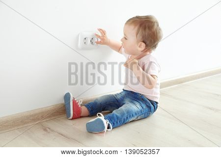 Baby playing with electrical outlet on floor at home stock photo