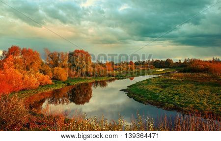 Autumn colorful view - sunset autumn picturesque landscape with autumn river and yellowed autumn trees in the autumn evening. Soft focus applied.