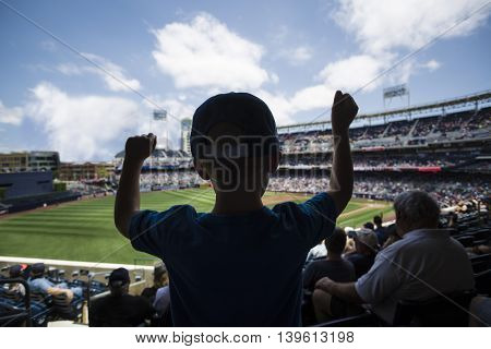 Child standing and cheering at a baseball game. Silhouette view from behind stock photo