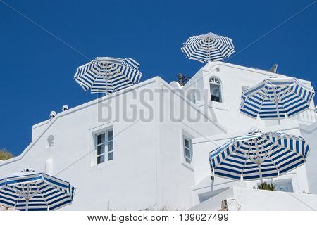 Cinco guardas-sol azuis e brancos listrados em hotel em Santorini Five blue and white striped Umbrellas at hotel in Santorini. Cinco parasoles azules y blancos rayados en hotel en Santorini.