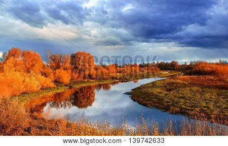 Autumn colorful water view of sunset autumn picturesque nature with autumn river and yellowed autumn trees in the autumn sunset. Soft filter processing.