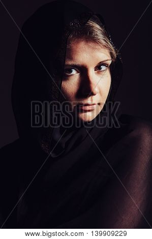 Portrait of beautiful woman with brown eyes wearing black scarf veil. Toned Image. stock photo