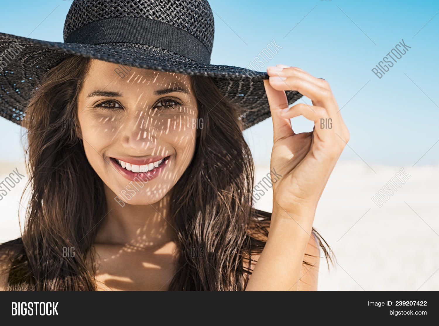 Portrait of beautiful young woman wearing summer black hat with large brim at beach. Closeup face of