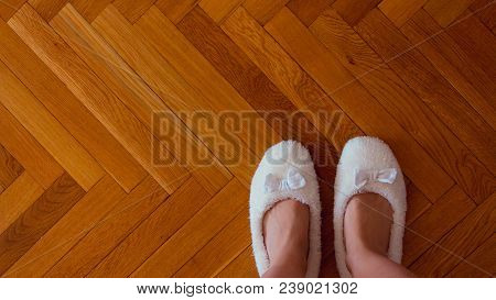Top view of female legs in white slippers on background of parquet floor at home stock photo