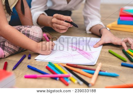Closed up hands of mom teaching little children to drawing cartoon in art class with color pen. Back to school and Education concept. Family and Home sweet home theme. Preschool kids theme stock photo