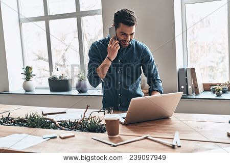 Good Business Talk. Handsome Young Man Talking On Smart Phone And Using Computer While Working In Th