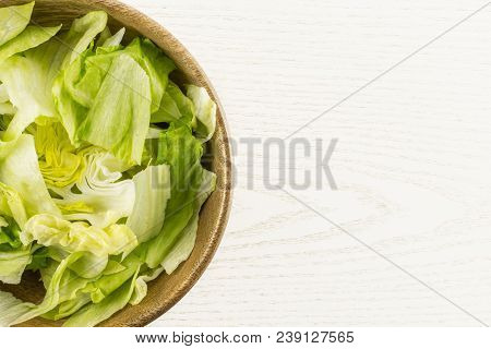 Iceberg lettuce fresh torn salad leaves in a wooden bowl table top isolated on grey wood background stock photo