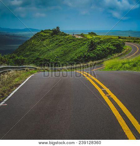 Curved road winding through the mountainous terrain of Waimea Canyon State Park, Kauai, Hawaii, United States stock photo