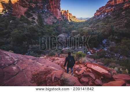 Male hiker descending a steep and rugged red rock tail from a scenic overlook of Fay Canyon, Coconino National Forest, Arizona stock photo