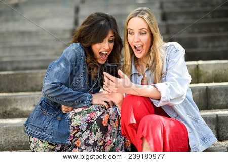 Two young women looking at some awesome thing on their smart phone outdoors, sitting on urban steps. Friends girls. stock photo