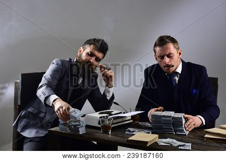 Company engaged in illegal business. Businessmen discussing illegal deal while drinking and smoking, grey background. Men sitting at table with piles of money and typewriter. Illegal business concept. stock photo