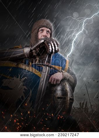 Lightning strikes a knight on battlefield. Knight with sword in battlefield. stock photo