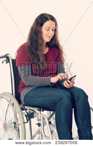 young woman in wheelchair using her smartphone stock photo