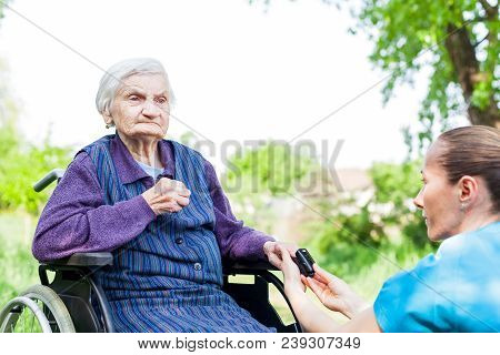 Young nurse measuring elderly woman's cardiac pulse with oximeter outdoor stock photo