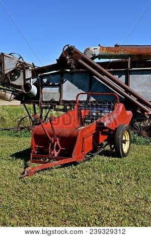 An old manure spreader is parked in from of an even older threshing machine. stock photo