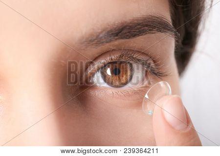 Young woman putting contact lens in her eye, closeup stock photo