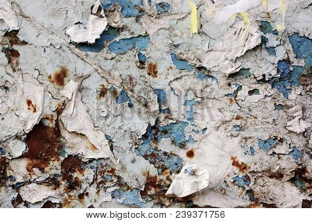 Old, torn bulletin board. Street empty public billboard, blue dirty wall with rust. Bright colorful background for your design. Advertisement hoarding with scraps of old ads. Horizontal orientation. stock photo