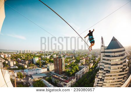A man is walking along a line. The persone follows a tight line between two tall buildings. Highline against the background of the city. stock photo