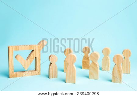 human figures stand together next to a tick in the box. The concept of elections and social technologies. Volunteers, parties, candidates, constituency electorates. Human rights. Selective focus stock photo