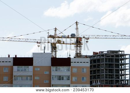 Large construction site including several cranes working on a building complex, with clear blue sky and the sun stock photo