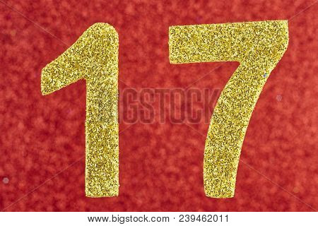 Number seventeen golden color over a red background. Anniversary. Horizontal stock photo