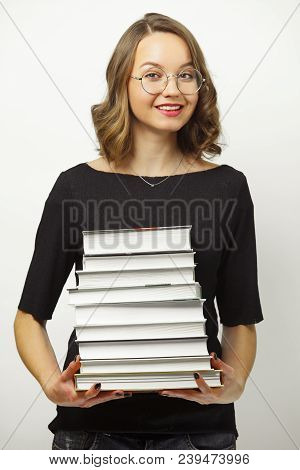 Portrait of attractive woman with stack of books in hands, has happy expression, passed the exams at the end of school or university, stands over white isolated background. Concept of successful applicant. stock photo