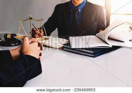 law and justice concept, Attorney or lawyer judgement lawsuit with holding pen, law book,gavel and scales of justice at table in office. stock photo