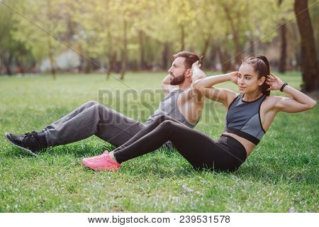 Strong and powerful people are working out outside in park. They are doing abs exercises. Young man and woman look serious and cocnentrated stock photo
