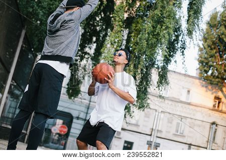 Two guys are training. The boy in white shirt is getting ready to throw the ball while the afroamerican guy is defencing the basket and trying to prevent ball hit the basket stock photo