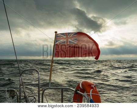 The uk red ensign the british maritime flag flown from yacht sail boat, blue sky and baltic sea. Summer and travel voyage stock photo