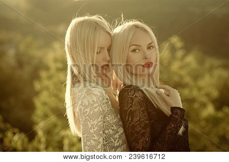 Sisters twins posing on sunny natural landscape. Two women with red lips and long blond hair. Contrasts and opposites concept. Dualism and dualistic nature. Beauty and fashion. stock photo