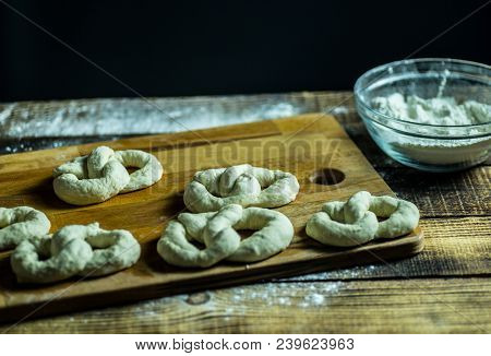 dough docked on the wooden board, traditional pretzel preparation, baker making bread dough in the bakery. hands played with flour and dough. stock photo