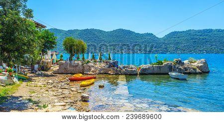 The colored kayaks and fishing boat on the rocky shore of Kekova Bay, Kalekoy, Turkey. stock photo