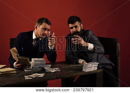 Company celebrates business profit, successful deal. Businessmen discussing illegal deal while drinking and smoking, red background. Men sitting at table with piles of money. Business success concept. stock photo