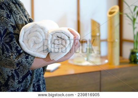 Chambermaid holding clean towels in spa. Clean white towel in a Spa centre. Staff cleaning lady holding towels at spa stock photo