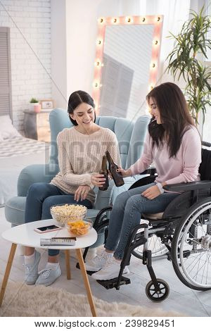 Cheers darling. Gay sister and immobile woman enjoying beer and talking stock photo