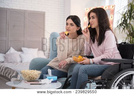 Sisters friendship. Attentive sister and immobile woman eating cheeps and regarding film stock photo