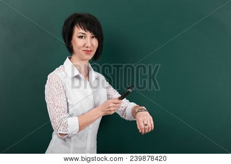 a woman looks through a magnifying glass on watch, a blackboard as a background, a concept of education and business stock photo