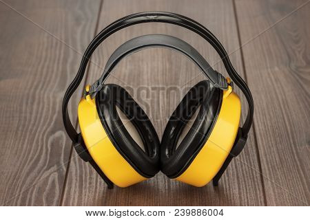 hearing protection yellow ear muffs on wooden table stock photo