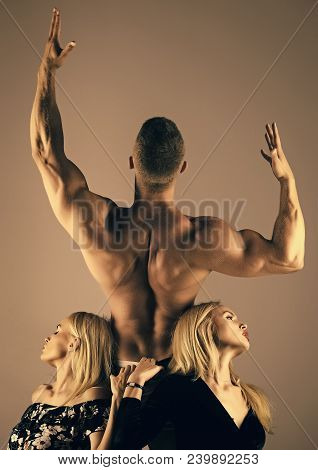 Man bodybuilder with muscular back raise hands biceps, triceps, and girls or women with long blond hair. Sport, fitness, diet, health concept. stock photo