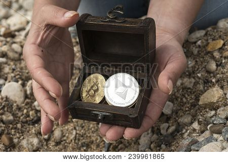 bitcoins and etherium. treasure trove in the chest in hand. cryptocurrency, bitcoin and etherium stock photo