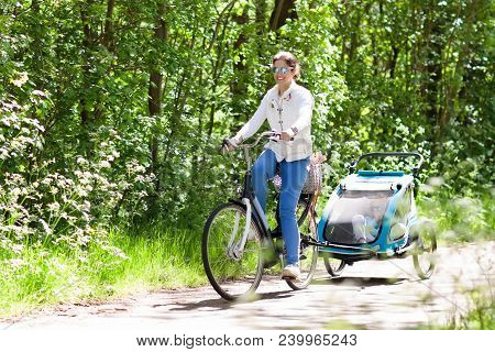 Young mother riding bicycle with baby bike trailer in sunny summer park. Fit active woman cycling with child. Safe transportation of little kids. Mom and children riding bikes. Family outdoor activity stock photo